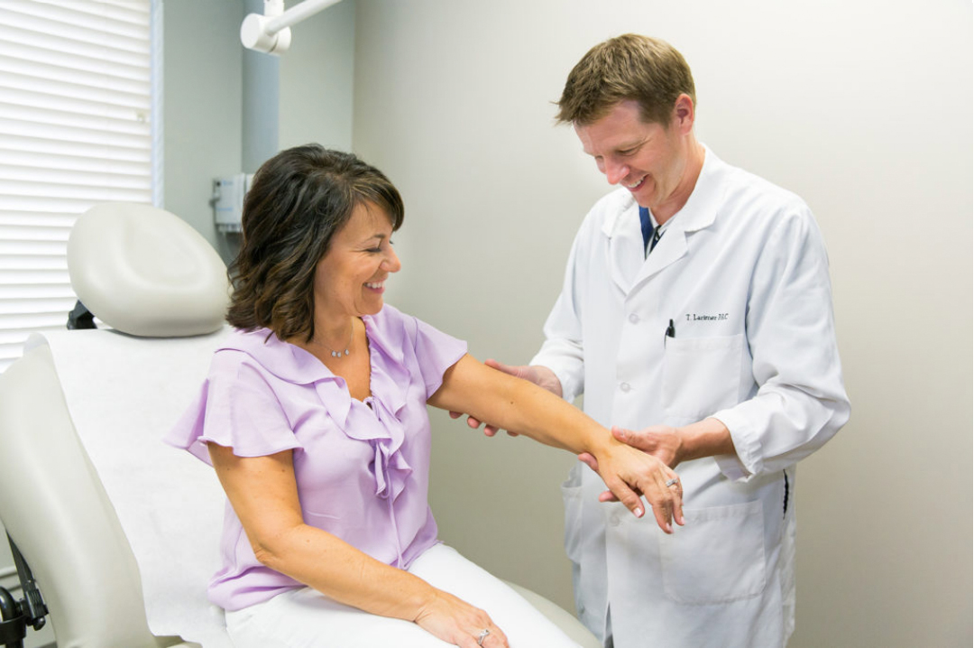 Picture of a dermatologist helping a patient.