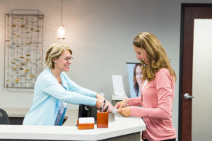 Picture of a dermatology patient talking with an employee at the front desk.